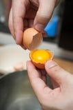 Los huevos que se agrietan y separan la yema de huevo de albumen imágenes de archivo libres de regalías