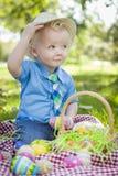 Los huevos que se sostienen exteriores lindos de Little Boy Pascua inclinan su sombrero Imagen de archivo