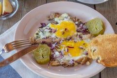 Los huevos revueltos con el tocino y las salmueras, pan tostado, untan con mantequilla imagen de archivo