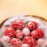 Los huevos rojos de Pascua con el modelo blanco popular ponen en pluma en cesta en el papel del vintage, abajo echan a un lado Hu Imágenes de archivo libres de regalías