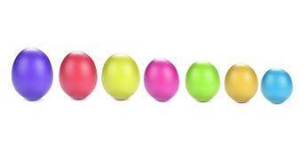 Los huevos teñieron el fondo blanco colorido Imagenes de archivo