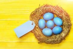 Los huevos tradicionales pintados en paja tejida interior azul del color enrruellan Imagen de archivo libre de regalías