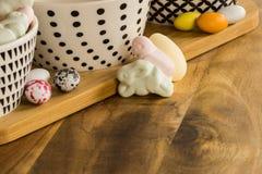 Los huevos y el animal de caramelo de Pascua formaron las melcochas en surfa de madera Foto de archivo