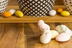 Los huevos y el animal de caramelo de Pascua formaron las melcochas en surfa de madera Imágenes de archivo libres de regalías