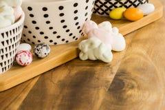 Los huevos y el animal de caramelo de Pascua formaron las melcochas en surfa de madera Imagen de archivo