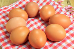 Los huevos y el paño en el fondo de madera Foto de archivo
