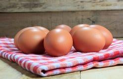 Los huevos y el paño en el fondo de madera de la falta de definición Foto de archivo