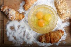 Los huevos y la hornada quebrados en la tarjeta de madera vertieron por una harina Imagenes de archivo