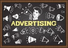 Los iconos dibujados mano del megáfono en la pizarra con la publicidad de la palabra y un hombre están anunciando Imagen de archivo