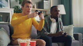 Los individuos afroamericanos y caucásicos están jugando hacer del videojuego después alto-cinco y la sacudida de las manos Tecno almacen de video