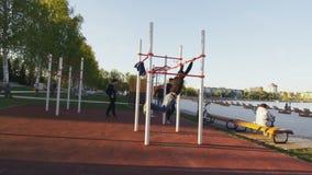 Los individuos atléticos entrenan en la tierra de deportes con las barras horizontales metrajes