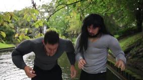 Los individuos divertidos en trajes falsos del músculo en el barco flotante golpearon ramas de árbol finas almacen de video