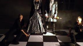 Los individuos heridos en ropa negra se arrastran detrás en el tablero de ajedrez El rey y la reina oscuros caen decepcionado sus metrajes