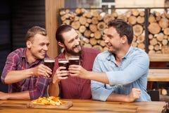 Los individuos jovenes alegres están descansando en cervecería Imagen de archivo libre de regalías