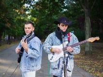 Los individuos jovenes felices cantan canciones y tocan la guitarra en una chaqueta de los vaqueros en un parque en un fondo natu Fotos de archivo