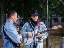 Los individuos jovenes felices cantan canciones y tocan la guitarra en una chaqueta de los vaqueros en un parque en un fondo natu Imágenes de archivo libres de regalías