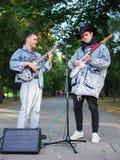 Los individuos jovenes felices cantan canciones y tocan la guitarra en una chaqueta de los vaqueros en un parque en un fondo natu Foto de archivo