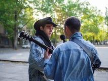 Los individuos jovenes felices cantan canciones y tocan la guitarra en una chaqueta de los vaqueros en un parque en un fondo natu Foto de archivo libre de regalías