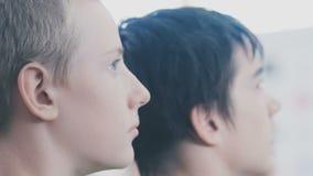 Los individuos jovenes miran a un lado almacen de video