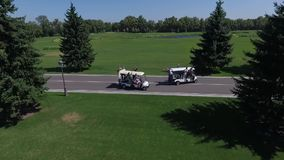 Los individuos se divierten en los coches del golf metrajes