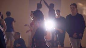 Los individuos y las muchachas jovenes realizan una danza teniendo en cuenta la lámpara en estudio almacen de video