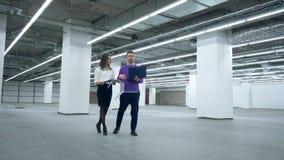 Los ingenieros caminan en un cuarto, trabajando con documentos y un ordenador portátil metrajes