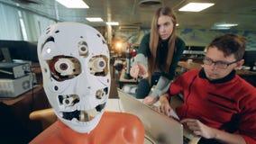 Los ingenieros comprueban una lengua móvil del robot Ingenieros que trabajan con el humanoid futurista, cyborg almacen de video