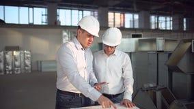 Los ingenieros de construcción consultan con la tableta de la pantalla táctil para el insite constructivo de la reunión de planif almacen de metraje de vídeo