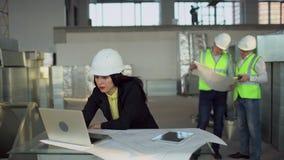 Los ingenieros de construcción hembra o el llevar de los arquitectos hicieron que los sombreros utilizaran el ordenador portátil  almacen de video