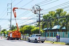 Los ingenieros de la electricidad en las elevaciones de Tailandia hasta fijan la electricidad Foto de archivo
