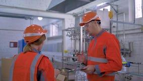 Los ingenieros de sexo femenino con el hombre en cascos con la tableta digital están comprobando la fábrica de la producción mien almacen de video