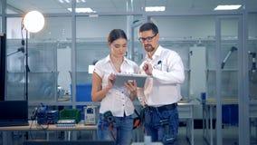 Los ingenieros de sexo femenino y de sexo masculino están discutiendo algo con una tableta almacen de video