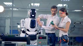Los ingenieros de sexo masculino y de sexo femenino están tomando lecturas de a humano-como el robot con el equipo especial metrajes
