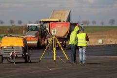 Los ingenieros del topógrafo están midiendo llano en una pista como parte del plan de expansión del aeropuerto internacional del  Imágenes de archivo libres de regalías