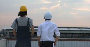 Los ingenieros en el tejado que ven igualando la visión almacen de metraje de vídeo