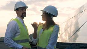 Los ingenieros hablan mientras que se colocan cerca de muchas baterías del sol 4K almacen de metraje de vídeo