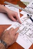 Los ingenieros, los arquitectos o los contratistas trabajan en planes Imágenes de archivo libres de regalías