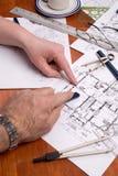 Los ingenieros, los arquitectos o los contratistas trabajan en planes Imagen de archivo