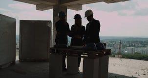 Los ingenieros o los arquitectos tienen una discusión en el emplazamiento de la obra que mira con el plan de la construcción jour almacen de metraje de vídeo
