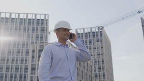 Los ingenieros son que controlan y de manejos de la construcción Él puso un casco blanco teléfono del uso para comunicar 4K almacen de video