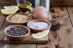 Los ingredientes de la mayonesa en la sal de madera del fondo sazonan los ingredientes rústicos del aceite con pimienta de limón  imagen de archivo libre de regalías