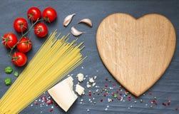 Los ingredientes de las pastas de los espaguetis resumen la comida en fondo negro Imagen de archivo