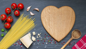 Los ingredientes de las pastas de los espaguetis resumen la comida en fondo negro Imagen de archivo libre de regalías