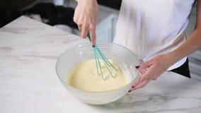 Los ingredientes de mezcla de la mujer irreconocible en el cuenco usando baten El cocinar hecho en casa Tiro a cámara lenta almacen de video