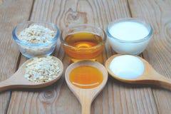 Los ingredientes naturales para la cara de cuerpo hecha en casa friegan la miel y el yogur de la avena Concepto de la belleza Imagen de archivo