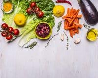 Los ingredientes para cocinar la comida vegetariana, calabaza, habas, tomates en una rama, limón, lechuga, cortaron la frontera d Foto de archivo libre de regalías