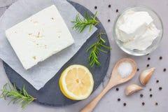 Los ingredientes para el queso Feta, el queso cremoso, el romero, el limón y el ajo sumergen a bordo, visión superior imagenes de archivo