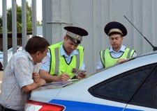 Los inspectores del servicio de la patrulla de la policía del camino hacen un informe en la violación de las reglas de tráfico Imágenes de archivo libres de regalías