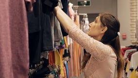 Los intentos bonitos jovenes de la muchacha eligieron mirada de moda de moda almacen de metraje de vídeo