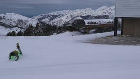 Los intentos de la persona para bajar la montaña en un monopatín a lo largo de la pista del esquí, pero bajan almacen de video